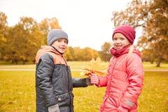 Le petit garçon donnant l'érable d'automne laisse à la fille Images stock