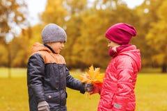 Le petit garçon donnant l'érable d'automne laisse à la fille Photographie stock