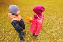 Le petit garçon donnant l'érable d'automne laisse à la fille Image libre de droits
