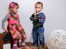 Le petit garçon donne à une fille une rose, d'isolement sur le blanc Images libres de droits