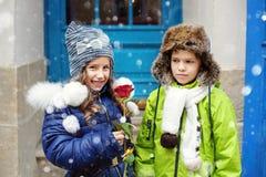 Le petit garçon donne à une fille une rose Deux enfants Le concept du jour d'amour et de ` s de Valentine photographie stock libre de droits