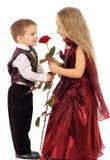 Le petit garçon donne à une fille une rose Image libre de droits