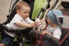 Le petit garçon donne la bouteille de fille avec de l'eau image libre de droits
