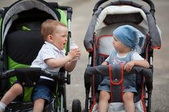Le petit garçon donne la bouteille d'eau à l'amie image stock