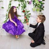 Le petit garçon donne une rose à la fille Amour d'enfants Photo stock