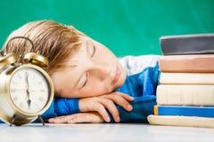 Le petit garçon dormant avec des livres s'approchent du tableau noir Photos stock