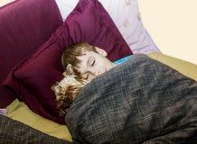 Le petit garçon dort dans le lit avec un petit chien Photographie stock libre de droits