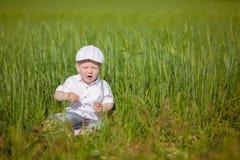 Le petit garçon drôle dans le chapeau blanc détendent dans l'herbe verte, à la PA d'été Image libre de droits