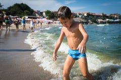 Le petit garçon drôle sort de la mer comme un zombi photographie stock libre de droits