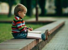 Le petit garçon drôle écrit avec le stylo Photographie stock