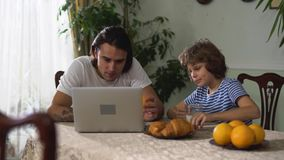 Le petit garçon eatting sur la table de cuisine et le cappuccino de boissons, puis donnent orange à son frère adulte Plus vieux e clips vidéos