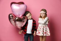 Le petit garçon ennuyé avec des ballons de coeur et a offensé peu de fille à la fête d'anniversaire ou à toute autre célébration images libres de droits