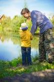 Le petit garçon est engagé dans la pêche dans un étang Enfant avec une laiterie i photo libre de droits