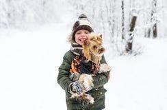 Le petit garçon et le petit chienchien en hiver se garent Photographie stock libre de droits