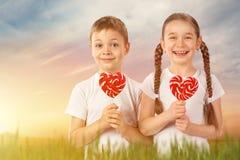 Le petit garçon et la fille avec la lucette rouge de sucrerie au coeur forment Jour du `s de Valentine Photo stock