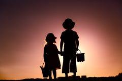 Le petit garçon et la fille avec la plage joue au coucher du soleil Images stock