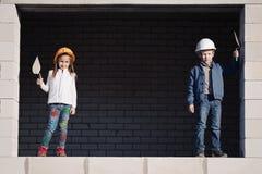 Le petit garçon et la fille dans les casques construisent la maison Photo libre de droits