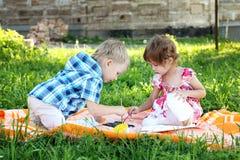 Le petit garçon et la fille mignons dessinent en stationnement d'été photos libres de droits