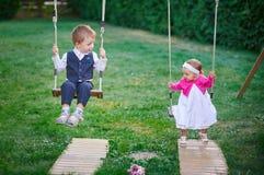 Le petit garçon et la fille montent en parc sur une oscillation Images stock