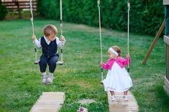 Le petit garçon et la fille montent sur une oscillation au terrain de jeu en parc photographie stock libre de droits