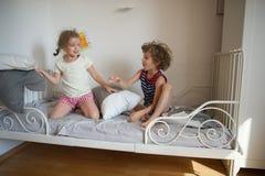 Le petit garçon et la fille ont présenté un combat d'oreiller sur le lit dans la chambre à coucher image libre de droits
