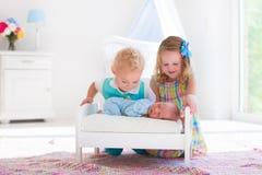 Le petit garçon et la fille rencontrent le nouvel enfant de mêmes parents Photo stock