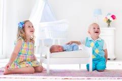 Le petit garçon et la fille rencontrent le nouvel enfant de mêmes parents Photographie stock
