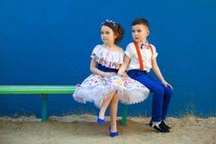 Le petit garçon et la fille s'asseyant au banc sont amoureux Images stock