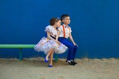 Le petit garçon et la fille s'asseyant au banc sont amoureux Photo stock