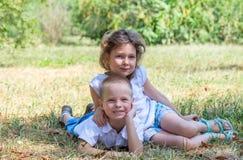 Le petit garçon et la fille se trouvent ensemble sur une herbe Images libres de droits