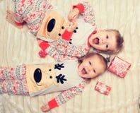 Le petit garçon et la fille se trouvent sur le lit dans des pyjamas Photos stock