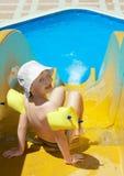 Le petit garçon et le waterslide Photographie stock libre de droits