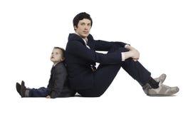 Le petit garçon et les hommes d'affaires communiquent, isolement Image stock