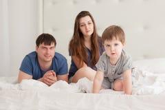 Le petit garçon et les parents sur des parents enfoncent les pyjamas de port Photos stock
