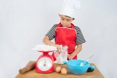 Le petit garçon faisant cuire la maison de gâteau a fait la boulangerie image stock