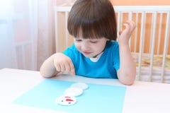 Le petit garçon fait le bonhomme de neige de la protection de coton Image stock