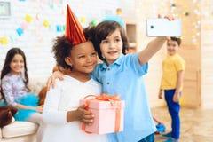 Le petit garçon fait le selfie avec la fille de joyeux anniversaire, qui tient le cadeau dans la boîte de fête image stock