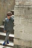 Le petit garçon fatigué se tient près du vieux mur avec l'escalier Photos stock