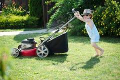 Le petit garçon fauche la pelouse avec la faucheuse photographie stock