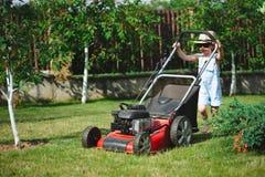 Le petit garçon fauche la pelouse avec la faucheuse photo stock