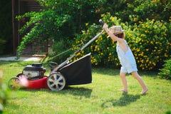 Le petit garçon fauche la pelouse avec la faucheuse photo libre de droits