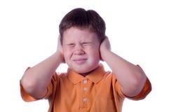Le petit garçon a fermé des mains d'oreilles Photos stock