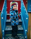 Le petit garçon gai se tient sur l'escalier au terrain de jeu images libres de droits