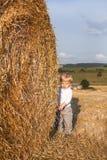 Le petit garçon goden dessus le gisement de foin Photographie stock libre de droits