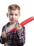 Le petit garçon gonfle le ballon, Image stock