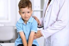 Le petit garçon heureux ayant l'amusement tandis qu'est examinent par le docteur par le stéthoscope Soins de santé, assurance et  Images libres de droits