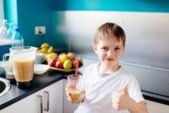 Le petit garçon heureux boit la macédoine de fruits selfmade Photos libres de droits