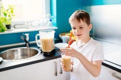 Le petit garçon heureux boit la macédoine de fruits selfmade Images stock