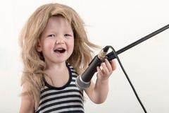 Le petit garçon heureux dans des vêtements intelligents chante une chanson avec un microphone à la maison Préparation au karaoke  images stock