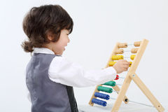 Le petit garçon heureux dans le gilet joue avec l'abaque coloré Photographie stock libre de droits